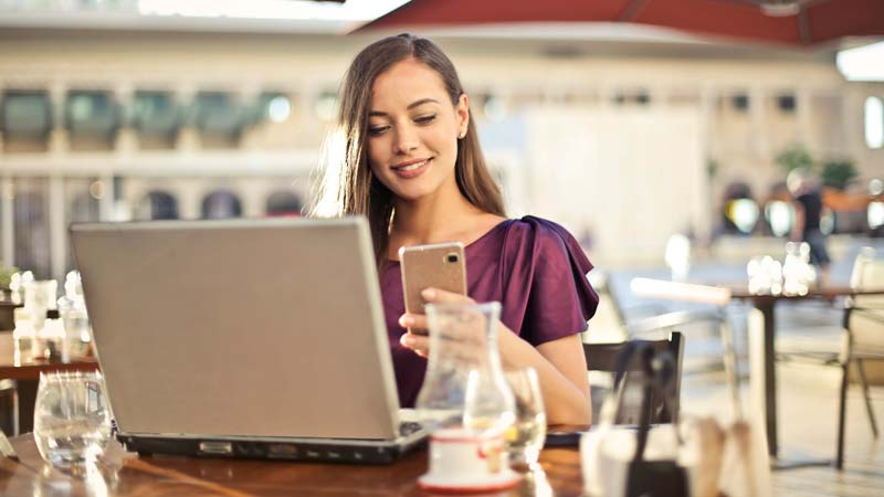 Woman using laptop and mobile
