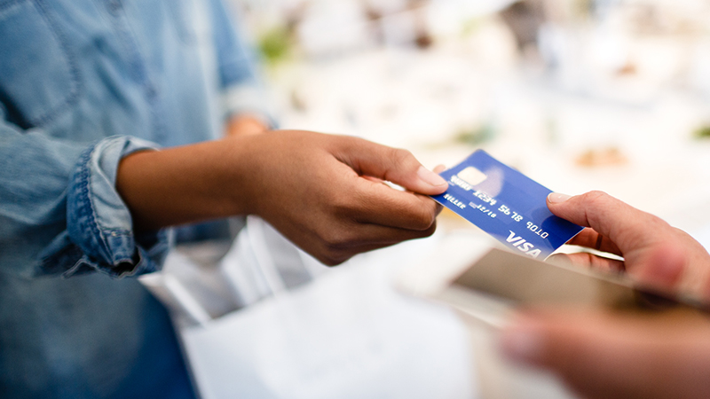 Woman handing off Visa Card to merchant.