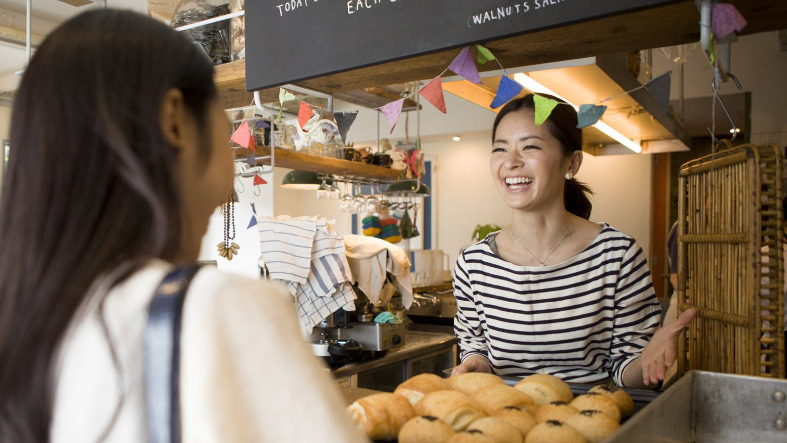 Women talking and laughing at bakery counter.