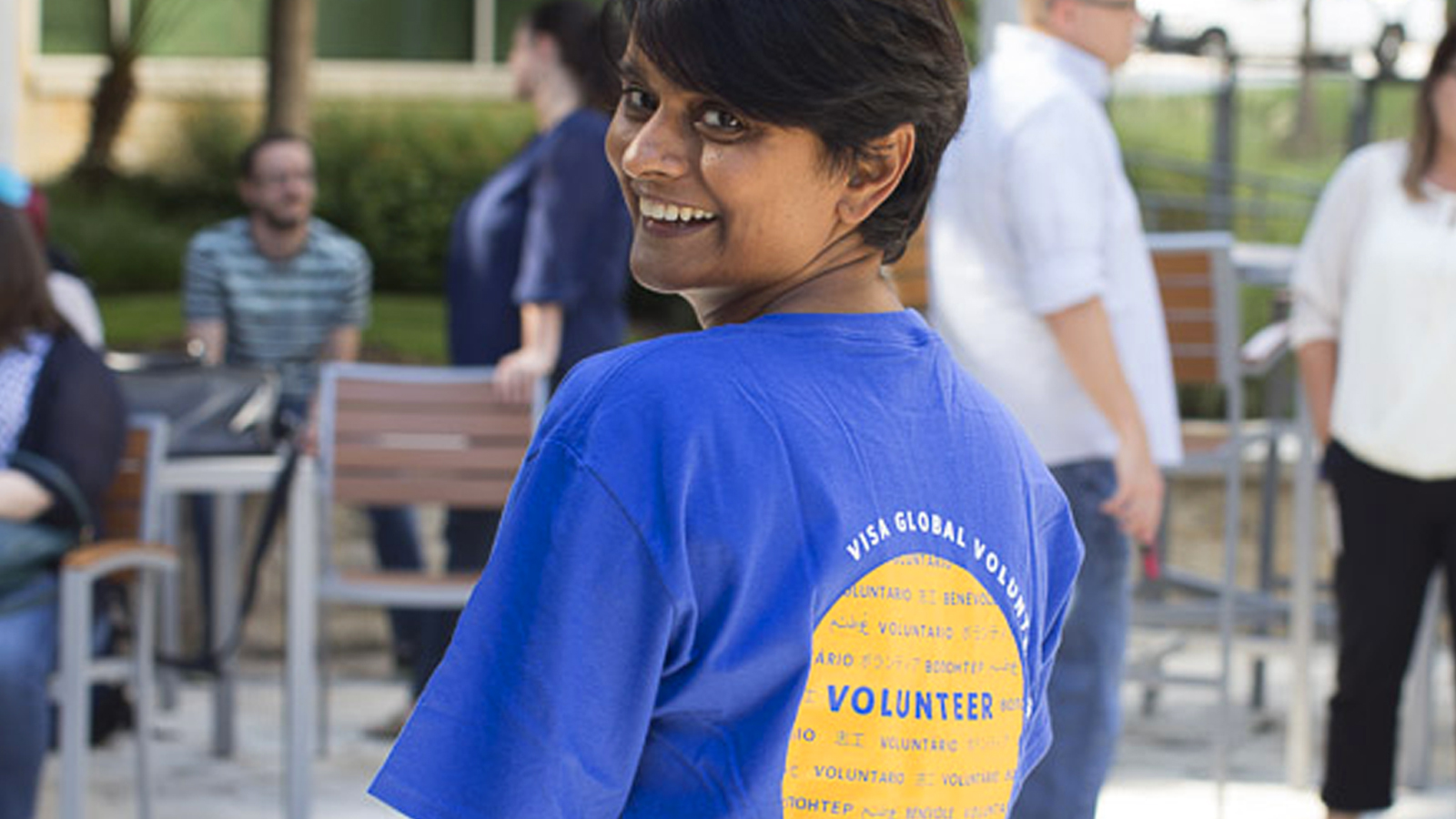 Visa volunteer smiling at camera with her back faced towards it.