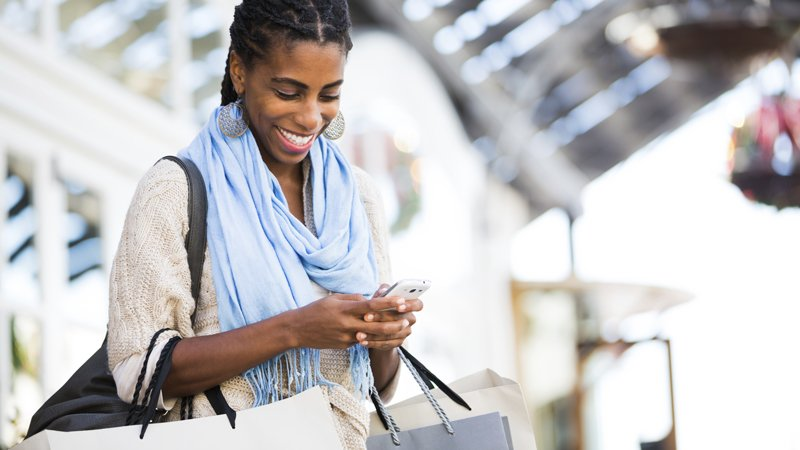 Woman using mobile phone while shopping.
