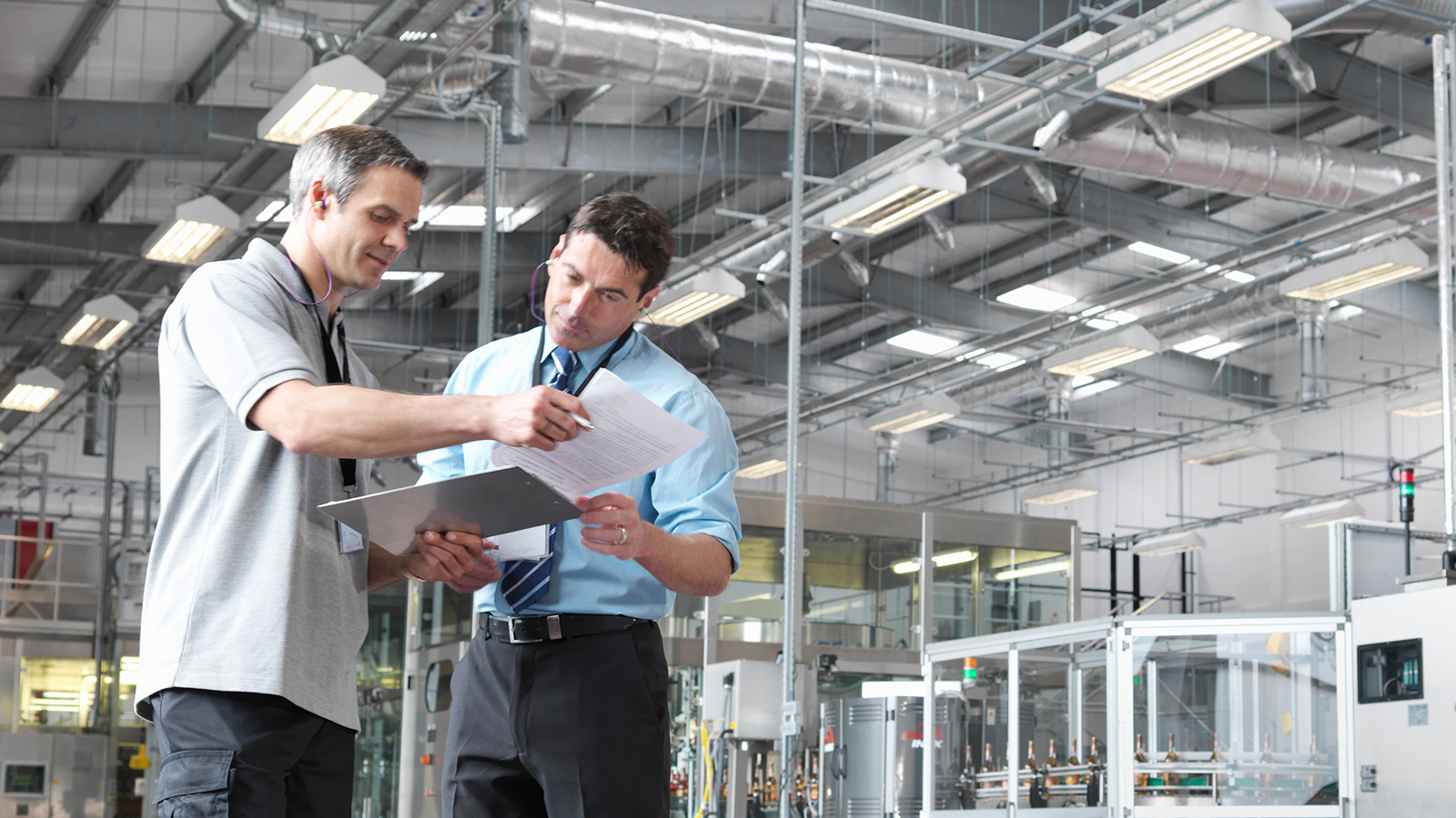 Two men discussing business in a factory