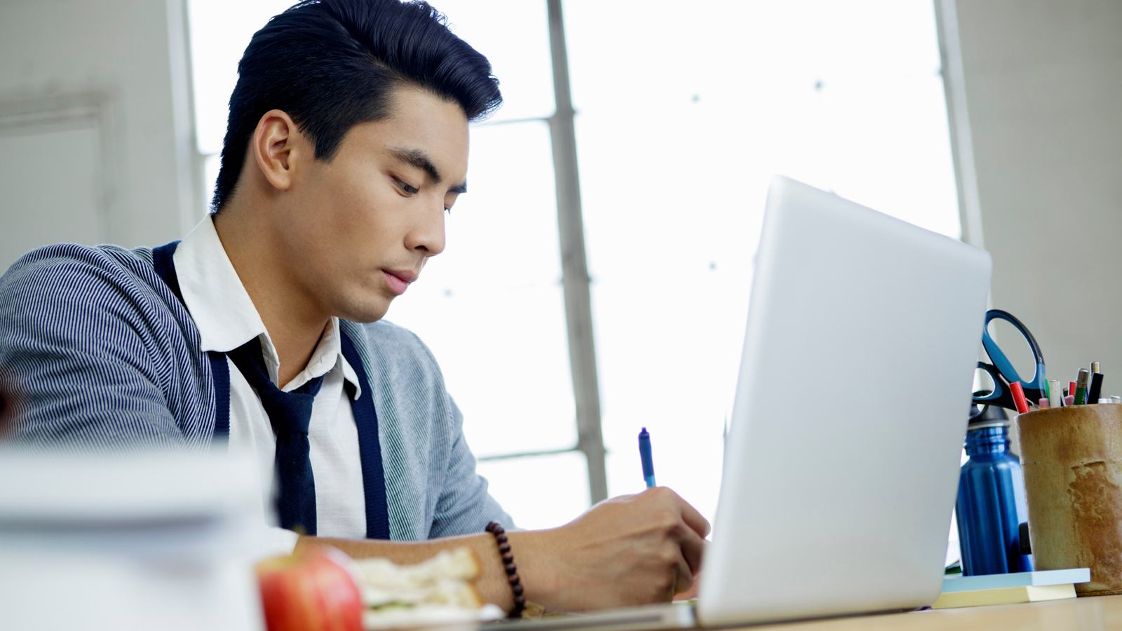 Man in front of laptop writing down notes