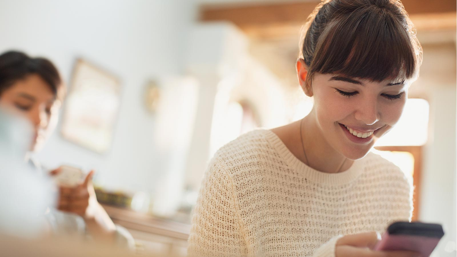 Woman smiling at her phone and making a payment on her device.